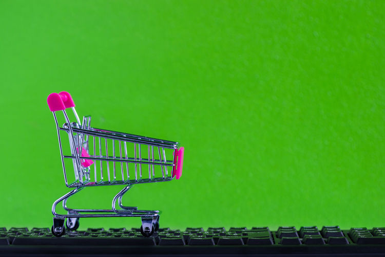 Close-Up Of Figurine Shopping Cart On Keyboard Against Green Background