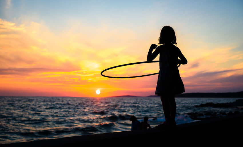 Girl is watching amazing sea sunset with hula hoop. Child is enjoying the sunset hooping, exercising and being active on a beach of island Silba in Croatia. Concept of healthy lifestyle in nature. Sunset Sky Sea Water Beauty In Nature Horizon Over Water Leisure Activity Outdoors Croatia Silba Watching People Girl Wall Adriatic Sea Lifestyles Silhuette Hulahoop Hula Hoop Hula Hooping  Plastic Hoop Hoopin Active Fitness Exercising