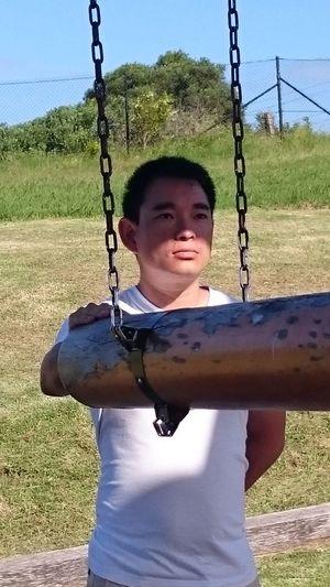 Portrait of boy on swing at playground