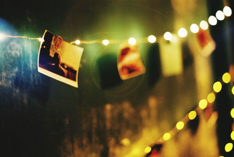 Close-up of photograph hanging from illuminated string lights