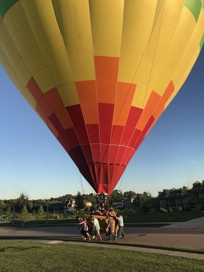 People by hot air balloon on field