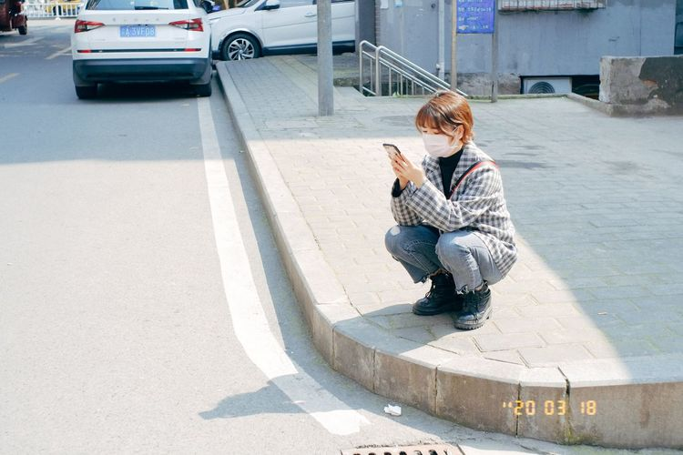 Full length of woman on sidewalk in city