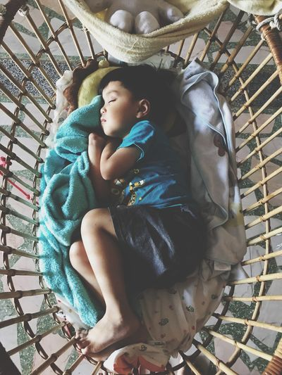 Directly above shot of girl sleeping in crib at home