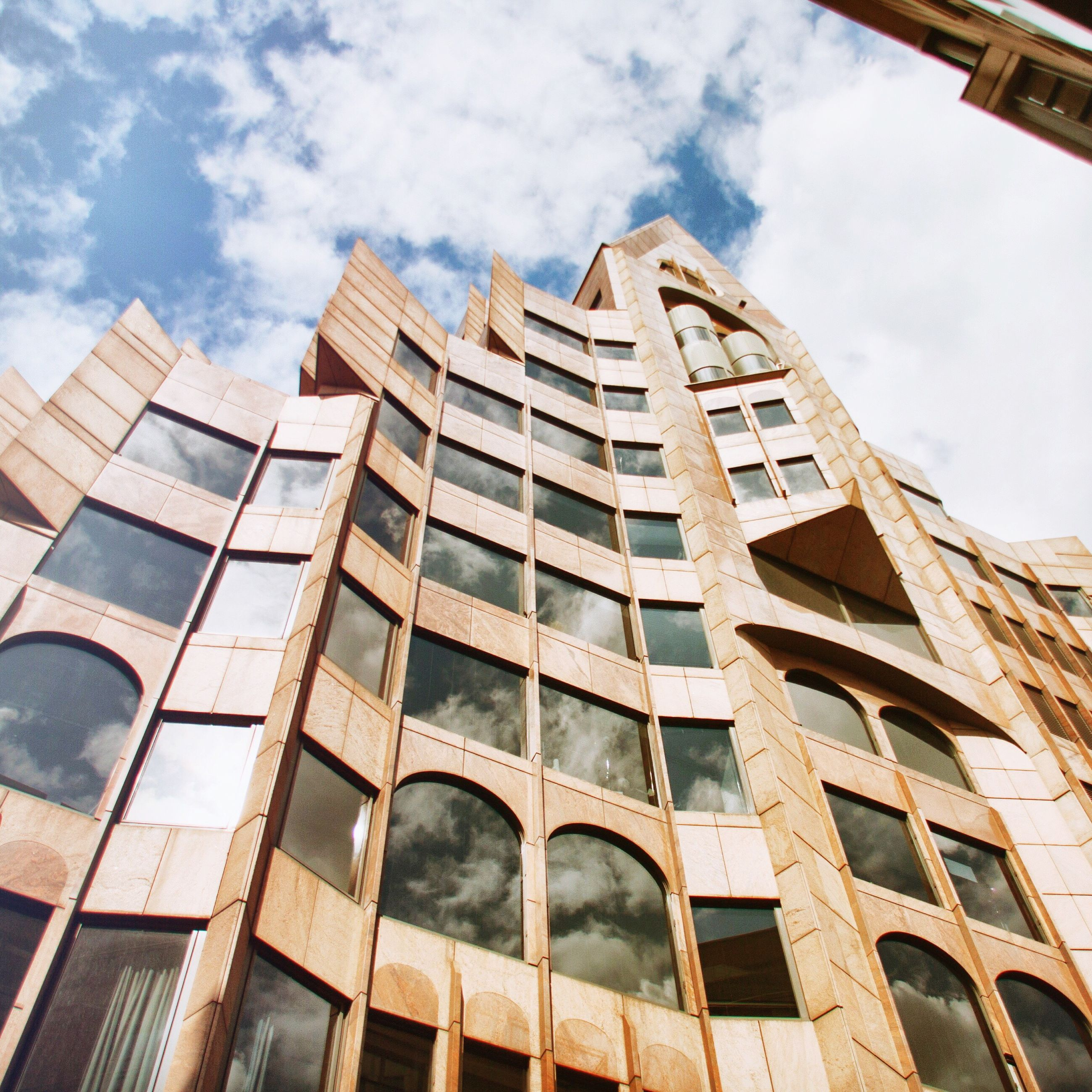 architecture, building exterior, built structure, low angle view, sky, window, cloud - sky, city, tall - high, office building, cloud, repetition, tower, building, skyscraper, in a row, modern, day, building story, outdoors, architectural feature, cloudy, tall, city life, geometric shape, spire, development, no people