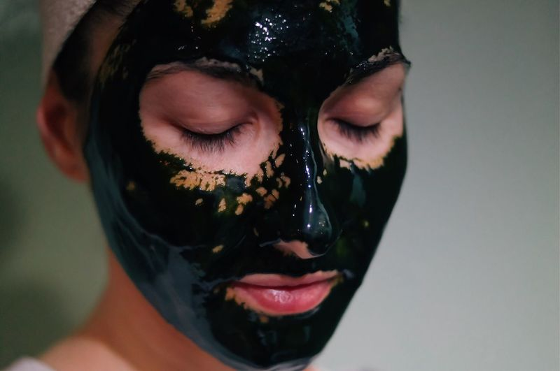 Young woman with eyes closed in facial mask against wall