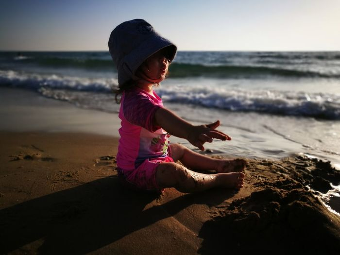 Boy gesturing while sitting at beach against sky