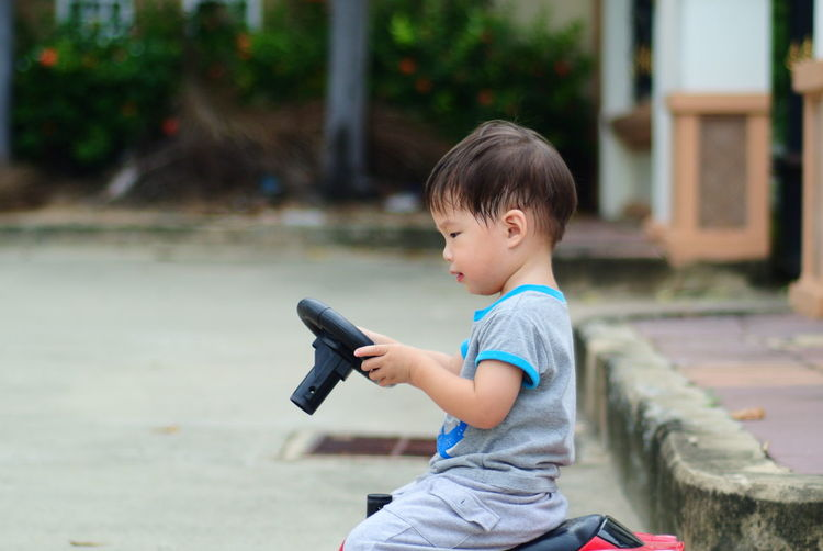 Side view of boy on toy car on footpath