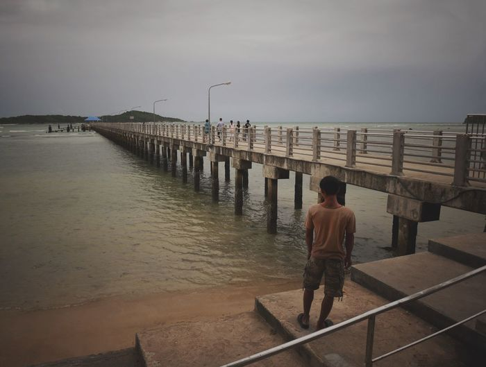 Rear view of man walking on pier at beach