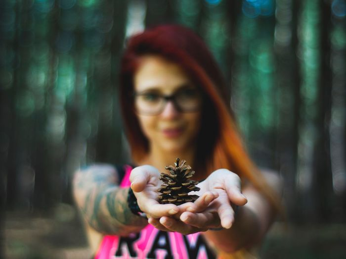 Portrait Of Woman Holding Pine Cone In Forest