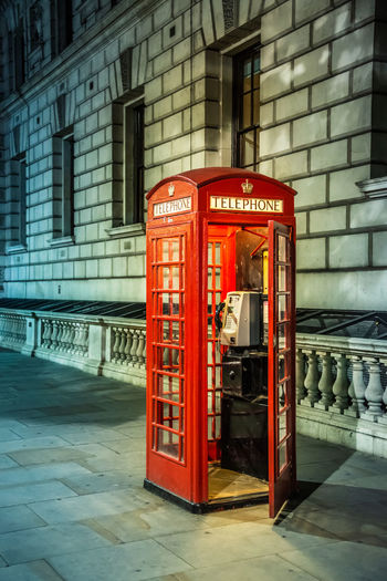 Red telephone booth on sidewalk