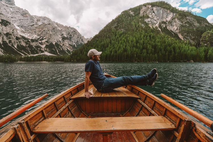 Man sitting on lake against mountains