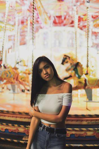 Portrait of young woman standing at amusement park