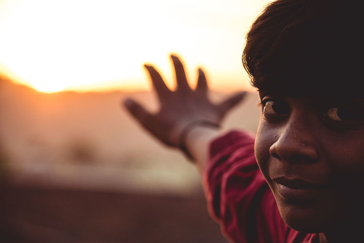 Close-up portrait of boy showing stop gesture