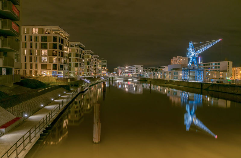 Reflection of buildings on river in illuminated city at night