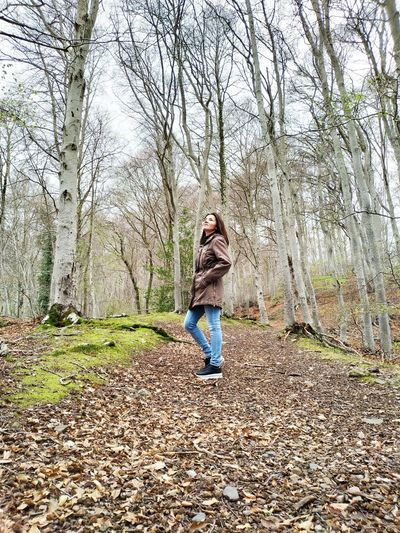 Full length of young woman standing at forest