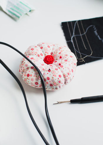 Colorful pin cushion with red button in the middle and stitch thread unpicker or sewing seam ripper with fabric scraps and cables of sewing machine on white crating table DIY Sewing Machine Cable Fabric High Angle View Indoors  Pin Cushion Scraps Seam Ripper Still Life Sweing White Tabke