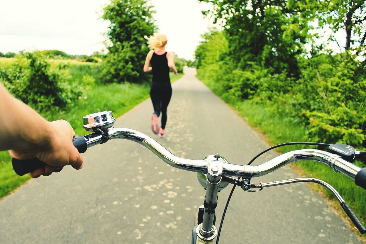 Close-up bicycle handlebar with woman running in distance