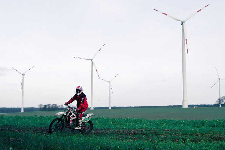 Person riding motocross by windmills on field against sky