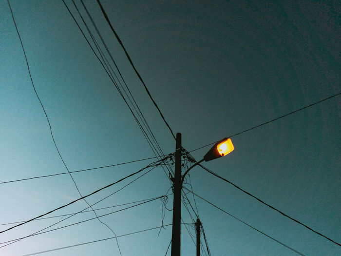 Low angle view of electricity pylon on street against sky