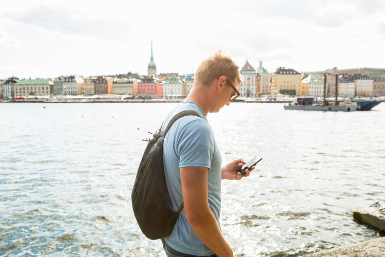 Man standing on mobile phone against river