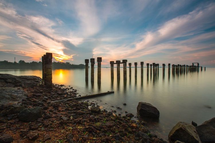 Abandoned pillar of jetty during sunrise at long exposure Sky Cloud - Sky Sunset Water Sea Architecture Reflection Day Building Exterior Horizon Over Water Beauty In Nature Beach Built Structure No People Nature Outdoors Scenics