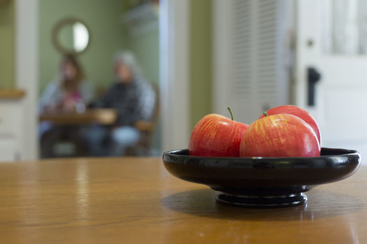 Horizontal image of apples on a wooden table in a kitchen with people sitting in the background. Blurred Out People In Background Bowl Close-up Day Focus On Foreground Food Food And Drink Freshness Fruit Healthy Eating Home Interior Indoors  One Person People Real People Table