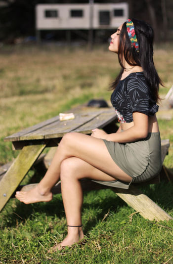 Full length of woman sitting on picnic table in grassy field