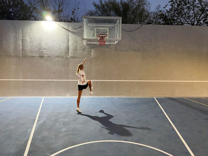 Woman at the basketball courts at night in action