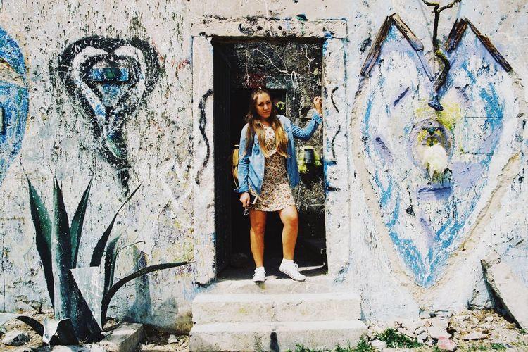 Portrait Of Young Woman Standing On Doorway