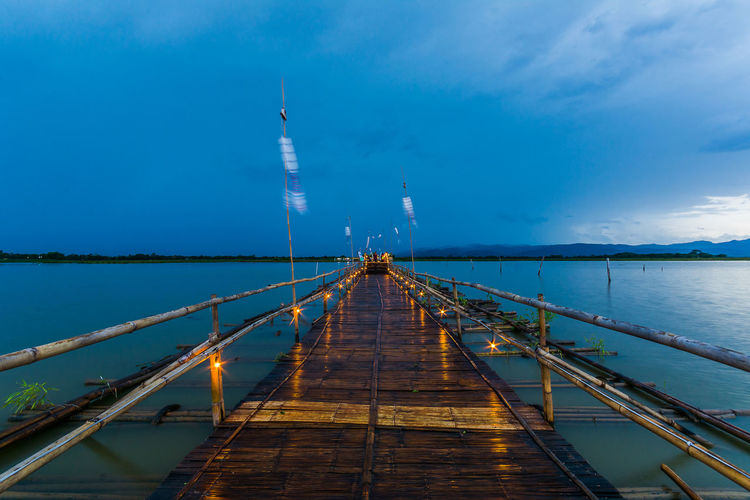Wooden pier in lake against cloudy sky