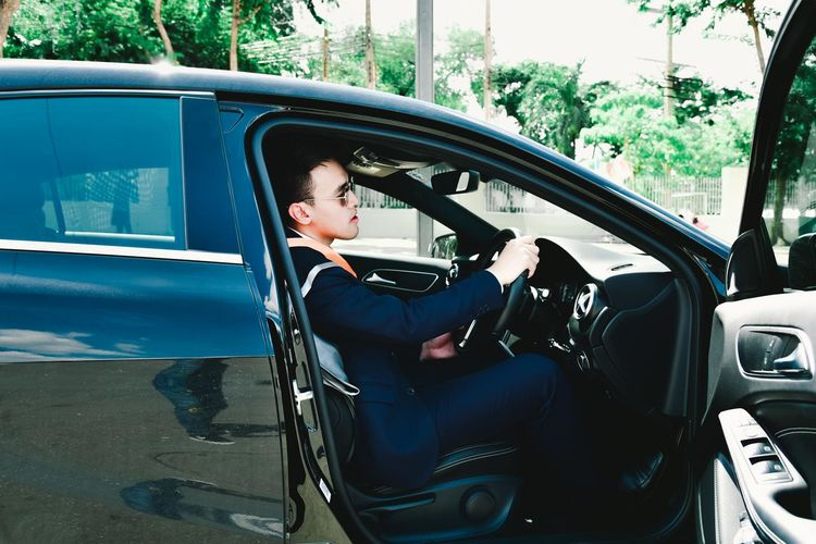 Side view of businessman sitting in car