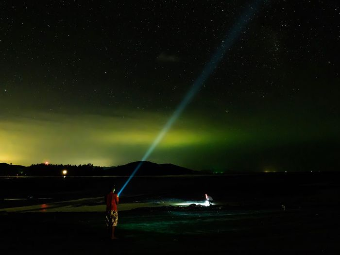 Rear view of man holding flashlight while standing at beach