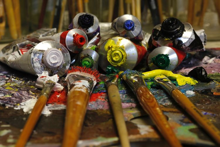 Close-Up Of Colorful Paint Tubes And Brushes On Palette
