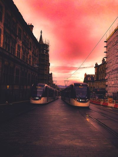 Myview MyArt MyPhotography Capital Cities  City Tram Public Transportation Red Color Redish Sky Architecture City Street Building Exterior Transportation Built Structure Sky Outdoors No People Road Land Vehicle Cloud - Sky City Street Dusk Building Mode Of Transportation Sunset Car Motor Vehicle Nature