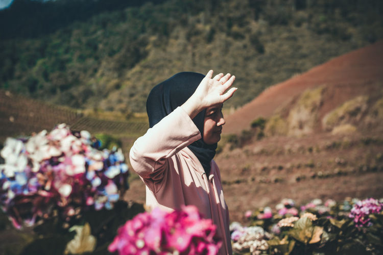 Woman gesturing while standing amidst flowers against mountains