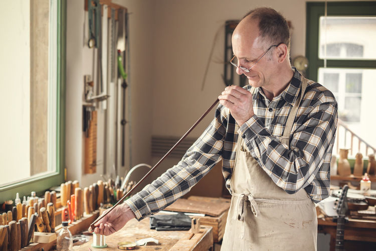 Instrument maker checking a violin bow with his eyes Candid Mature Men Real People Glasses Waist Up Professional Occupation Workbench Apron 50 Years Old Man Mature Adult Adult Concentration Skill  One Person Men Craftsperson Workshop Craft Indoors