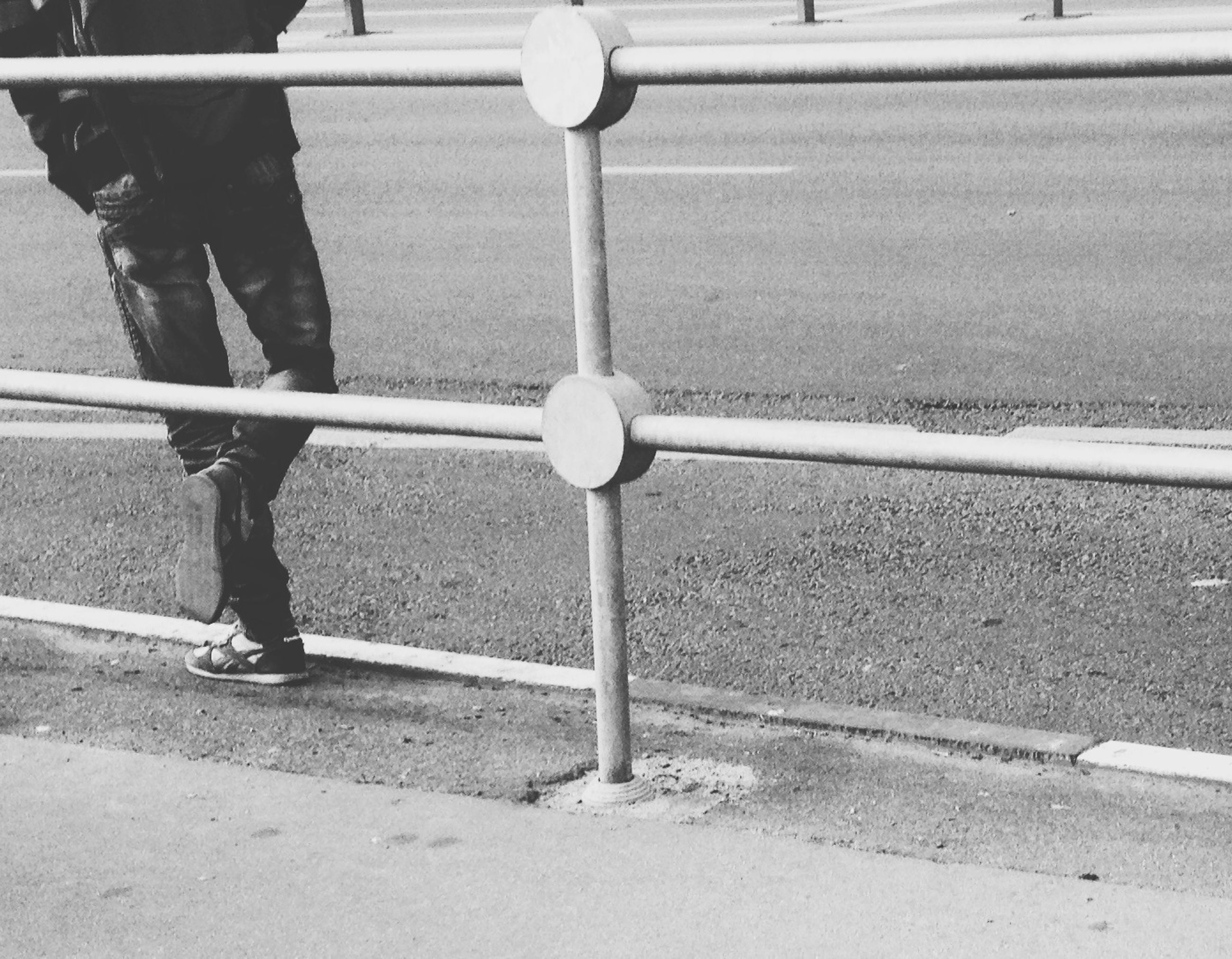 street, walking, metal, day, railing, standing, fence, outdoors, men, road, sidewalk, sunlight, protection, full length, safety, lifestyles, low section, shadow
