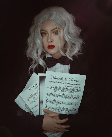 Portrait Of Young Woman Holding Sheet Music Against Black Background