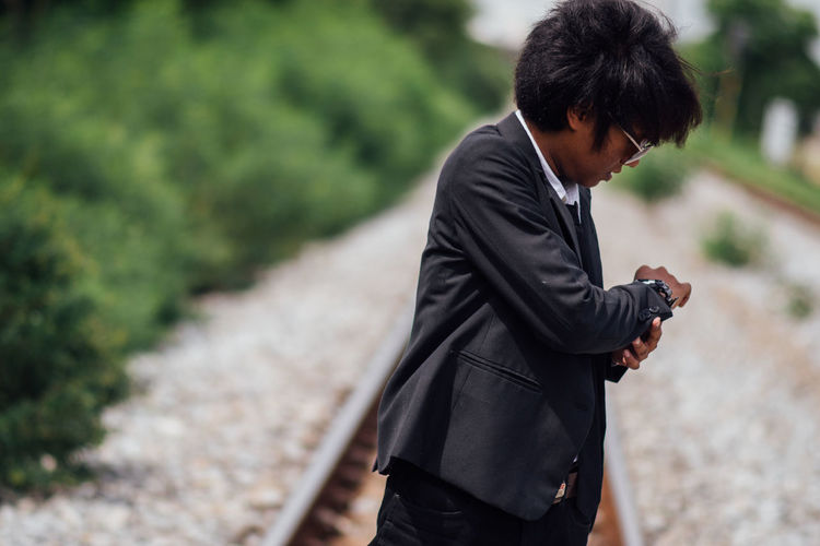 Businessman checking time on railroad track