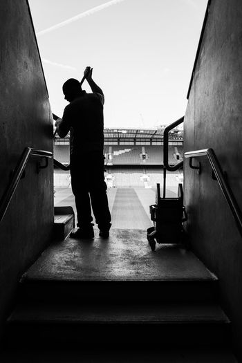 Arena Backlight Business Stories Cleaner Silhouette Stadium Steps Worker Adult Black And White Black And White Photography Bleachers Day Equipment Football Stadium Full Length One Man Only One Person People Real People Rear View Scrubbing Seats Standing