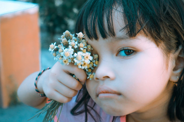 Close-up portrait of girl holding white flower outdoors