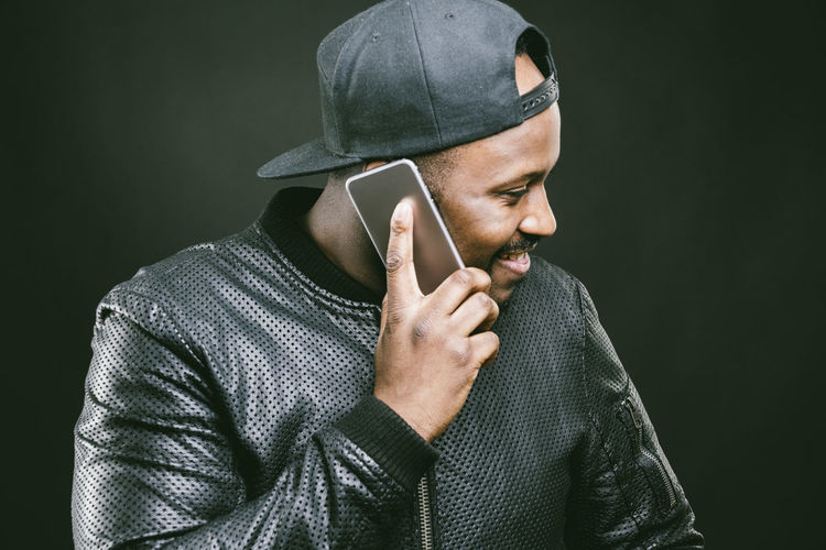 Man Talking On Mobile Phone Against Wall