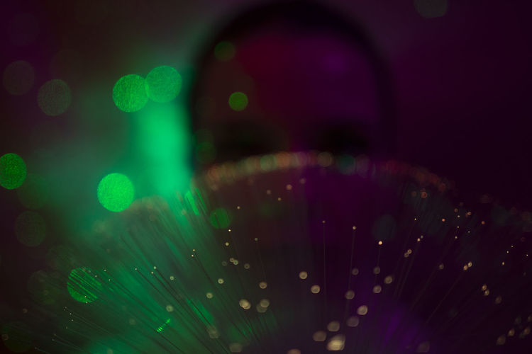 Defocused image of illuminated lights against black background