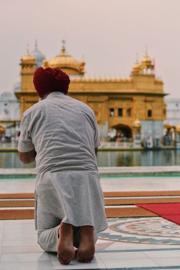 Rear view of man and woman at golden temple in city