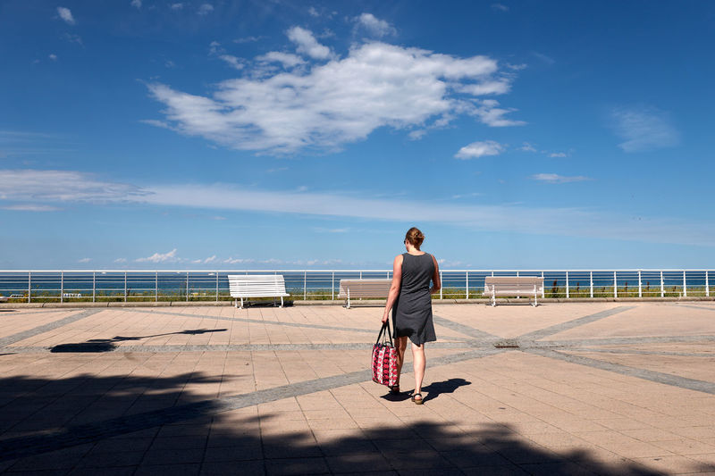 Rear view full length of woman walking at promenade on sunny day
