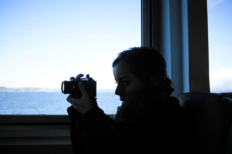 Young woman photographing through camera against clear sky