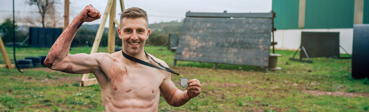 Portrait of shirtless man holding medal on land