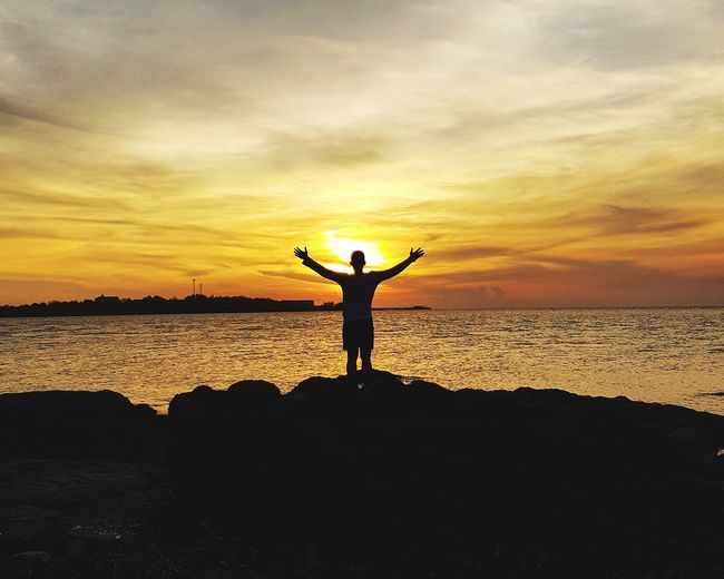 Silhouette man standing on rock at sea shore against sky during sunset