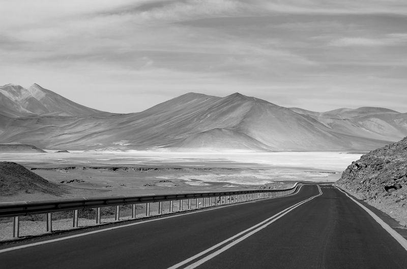 Monochrome empty road to the amazing highland salt lakes in northern chile, south america