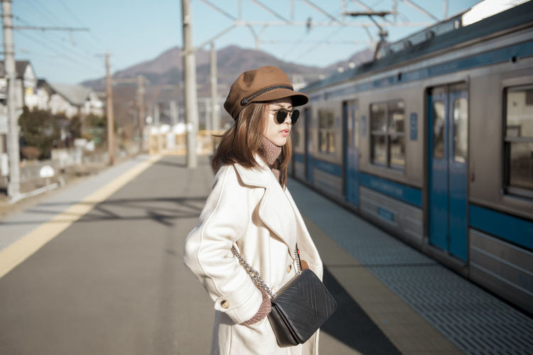Side view of young woman wearing hat standing on railroad station